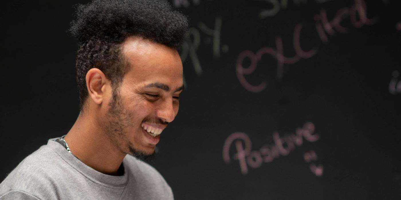 young man smiling in front of chalk board with words 'positive' 'excited' written on